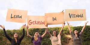 "Four young women holding signs that say ""Learn German in Vienna"""